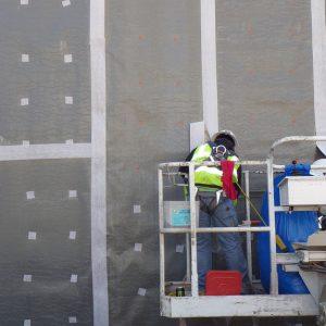 Worker installing Carlisle MiraPly V waterproofing membrane